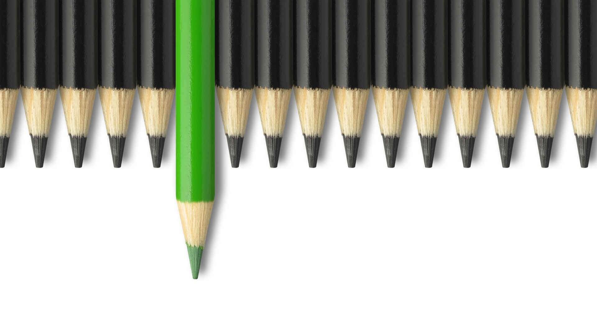 Green pencil standing out from crowd of black pencils